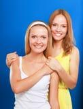 Portrait de plan rapproché du sourire de deux femmes d'isolement sur le fond bleu Images stock