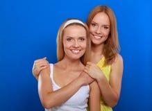 Portrait de plan rapproché du sourire de deux femmes d'isolement sur le fond bleu Photos libres de droits