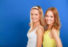 Portrait de plan rapproché du sourire de deux femmes d'isolement sur le fond bleu Photographie stock
