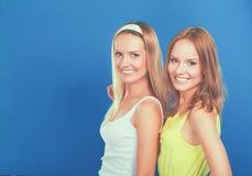 Portrait de plan rapproché du sourire de deux femmes d'isolement sur le fond bleu Image libre de droits