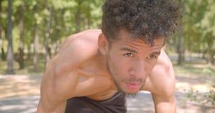 Portrait de plan rapproché du taqueur masculin de jeune Afro-américain d'ajustement préparant pour courir en parc étant déterminé clips vidéos