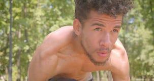 Portrait de plan rapproché du taqueur masculin de jeune Afro-américain sans chemise préparant pour courir en parc étant déterminé banque de vidéos