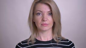 Portrait de plan rapproché du visage femelle caucasien attrayant adulte regardant la caméra avec le fond d'isolement sur le blanc banque de vidéos