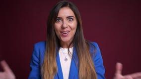 Portrait de plan rapproché de femelle caucasienne attirante dans l'habillement formel obtenant étonné et excité regardant la camé clips vidéos