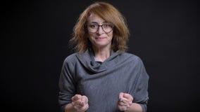 Portrait de plan rapproché de femelle rousse exagérée d'une cinquantaine d'années en verres étant excités et célébrant le moment  images libres de droits