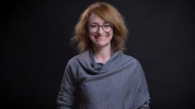 Portrait de plan rapproché de femelle rousse exagérée d'une cinquantaine d'années en verres étant heureux et souriant gaiement to images stock