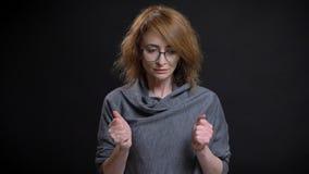 Portrait de plan rapproché de femelle rousse exagérée d'une cinquantaine d'années en verres étant inquiétés et nerveux serrant se images libres de droits
