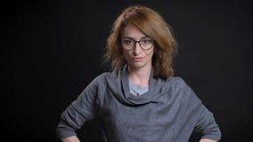 Portrait de plan rapproché de femelle rousse exagérée d'une cinquantaine d'années en verres ayant des mains sur les hanches et po image libre de droits