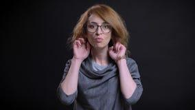 Portrait de plan rapproché de femelle rousse exagérée d'une cinquantaine d'années en verres faisant une expression du visage drôl photos stock