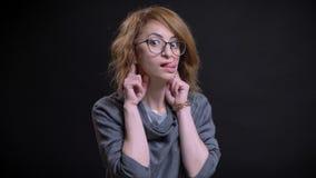 Portrait de plan rapproché de femelle rousse exagérée d'une cinquantaine d'années en verres faisant une expression du visage et u image stock