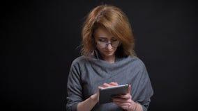 Portrait de plan rapproché de femelle rousse exagérée d'une cinquantaine d'années en verres textotant sur le comprimé devant la c images stock