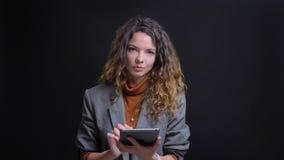 Portrait de plan rapproché de femme d'affaires attirante dactylographiant sur le comprimé regardant la caméra et le sourire banque de vidéos