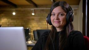 Portrait de plan rapproché de femme d'affaires caucasienne adulte dans des écouteurs devant la musique de écoute d'ordinateur por banque de vidéos
