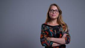 Portrait de plan rapproché de jeune femelle caucasienne sûre en verres faisant croiser ses bras au-dessus du coffre et regardant  clips vidéos
