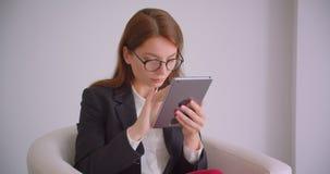 Portrait de plan rapproché de jeune femme d'affaires caucasienne en verres textotant sur le comprimé se reposant dans le fauteuil clips vidéos