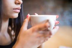 Portrait de plan rapproché de jeune femme tenant une tasse de café dans des mains photographie stock