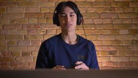 Portrait de plan rapproché de jeune homme coréen attirant dans des écouteurs jouant des jeux vidéo et échouant le niveau à l'inté banque de vidéos