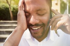 Portrait de plan rapproché de jeune homme d'affaires afro-américain drôle heureux utilisant le téléphone portable extérieur Fond  Image libre de droits