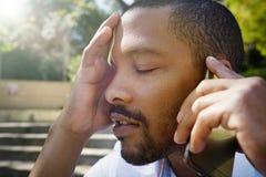 Portrait de plan rapproché de jeune homme d'affaires afro-américain fatigué utilisant le téléphone portable extérieur Photographie stock