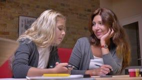 Portrait de plan rapproché de jeune mère caucasienne et son petit joli de dessin de fille parlant et passant le temps ensemble à banque de vidéos