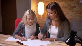 Portrait de plan rapproché de jeune mère et sa petite jolie de fille jouant un jeu d'orteil de tac de tic sur le papier ensemble  clips vidéos