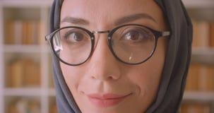 Portrait de plan rapproché de jeune visage femelle musulman en verres et de hijab regardant la caméra souriant gaiement dans la b clips vidéos
