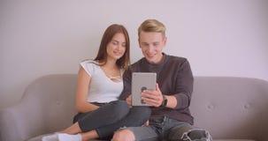 Portrait de plan rapproché de jeunes couples caucasiens mignons ayant un faire appel visuel au comprimé parlant ensemble se repos banque de vidéos
