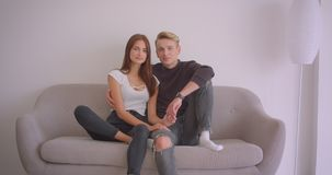 Portrait de plan rapproché de jeunes couples caucasiens regardant la caméra souriant gaiement étreignant la séance sur le divan à clips vidéos