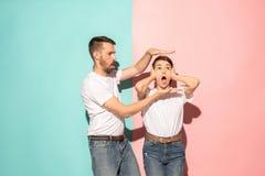 Portrait de plan rapproché de jeunes couples, homme, femme Concept de fan de TV sur le fond rose et bleu Contrastes d'émotion image libre de droits