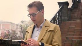 Portrait de plan rapproché de l'homme caucasien attirant passant en revue à son téléphone et se tenant en parc dehors clips vidéos