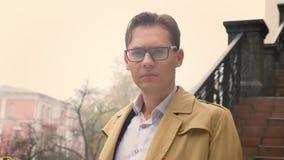 Portrait de plan rapproché de l'homme caucasien attirant regardant du côté et puis directement la position de caméra en parc deda banque de vidéos