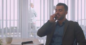 Portrait de plan rapproché de l'homme d'affaires attirant ayant un appel téléphonique parlant gaiement dans le bureau à l'intérie banque de vidéos