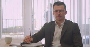 Portrait de plan rapproché de l'homme d'affaires attirant en verres regardant la caméra souriant gaiement dans le bureau à l'inté banque de vidéos