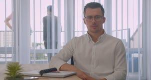 Portrait de plan rapproché de l'homme d'affaires attirant en verres regardant la caméra souriant gaiement se reposant au bureau d banque de vidéos