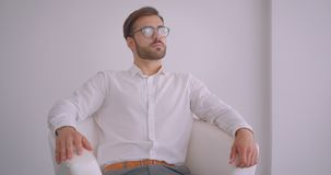 Portrait de plan rapproché de l'homme d'affaires caucasien barbu bel adulte s'asseyant dans le fauteuil dans le bureau blanc à l' banque de vidéos