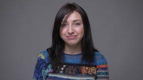 Portrait de plan rapproché de la femelle caucasienne adulte de brune souriant avec la confusion regardant la caméra avec le fond  banque de vidéos