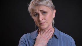 Portrait de plan rapproché de la femelle caucasienne attirante adulte ayant une gorge malade et étant malade tout en regardant la images libres de droits