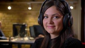 Portrait de plan rapproché de la femme d'affaires caucasienne adulte dans des écouteurs tournant et regardant la caméra souriant  banque de vidéos