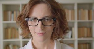 Portrait de plan rapproché de la femme d'affaires caucasienne attirante rousse adulte regardant la caméra souriant gaiement à l'i banque de vidéos