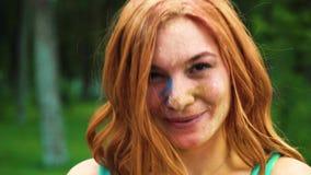 Portrait de plan rapproché de la fille d'une chevelure rouge dans la poudre de festival de Holi riant de la caméra banque de vidéos