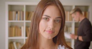 Portrait de plan rapproché de la jeune étudiante caucasienne regardant la caméra souriant gaiement dans la bibliothèque avec un j banque de vidéos