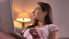 Portrait de plan rapproché de la jeune adolescente attirante écoutant la musique dans des écouteurs entreprenant des démarches et clips vidéos