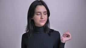 Portrait de plan rapproché de la jeune belle femelle aux cheveux noirs caucasienne étant ennuyée et faisant un bâillement devant  banque de vidéos