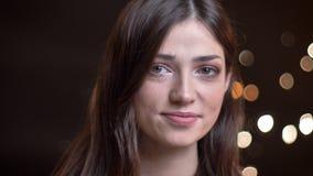 Portrait de plan rapproché de la jeune belle femelle sûre souriant et regardant la caméra avec des lumières de nuit sur le fond clips vidéos