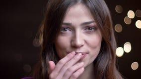 Portrait de plan rapproché de la jeune femelle caucasienne avec du charme faisant un baiser d'air et souriant tout en regardant l clips vidéos