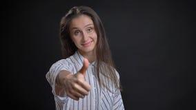 Portrait de plan rapproché de la jeune femelle caucasienne mignonne avec des cheveux de brune faisant des gestes le pouce et sour images stock
