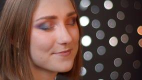Portrait de plan rapproch? de la jeune femelle caucasienne mignonne regardant la cam?ra et souriant joyeux avec le fond de bokeh banque de vidéos