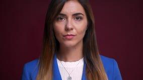 Portrait de plan rapproché de la jeune femelle caucasienne sûre attirante se tournant du côté vers la caméra et regardant directe banque de vidéos