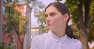 Portrait de plan rapproché de la jeune femme caucasienne attirante regardant la caméra se reposant gaiement en parc dehors clips vidéos