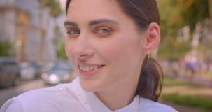 Portrait de plan rapproché de la jeune femme caucasienne attirante regardant la caméra souriant gaiement se reposant avec plaisir clips vidéos